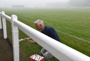 Peinture de la main courante qui entoure le terrain de football du Haut Champ